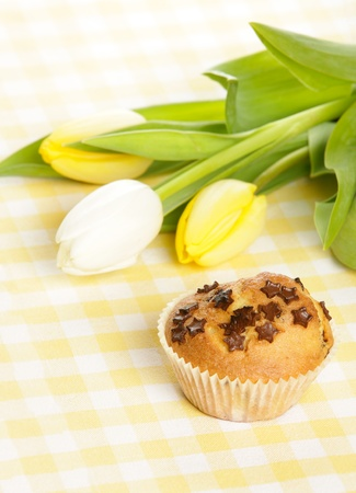 Home baked muffin with tulips in background photo