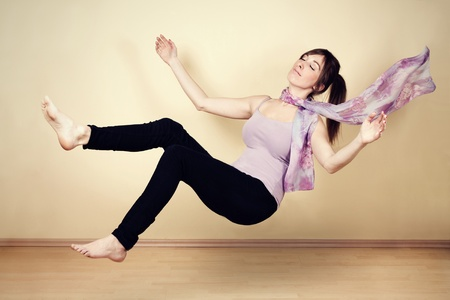 Young woman levitating in empty room