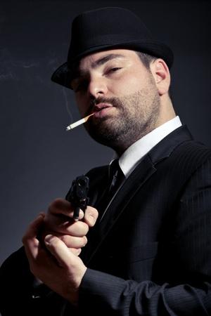 Dangerous man in suit with a gun photo