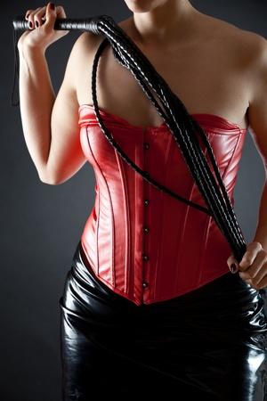 Szexi nő vörös bőr fűző, fekete ostor Stock fotó