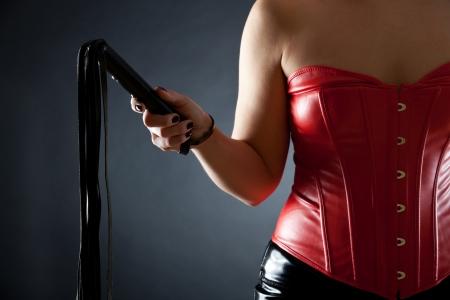 Sexy Frau in rotem Leder Korsett mit schwarzen Peitsche Standard-Bild