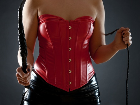 Sexy woman in red leather corset with black whip Stock Photo - 12639414