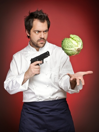 Male cook with gun pointing at savoy cabbage Stock Photo - 12590263