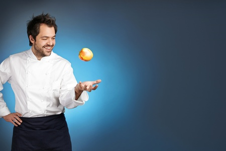 Young chef playing with apple agaist blue background Stock Photo - 12590260