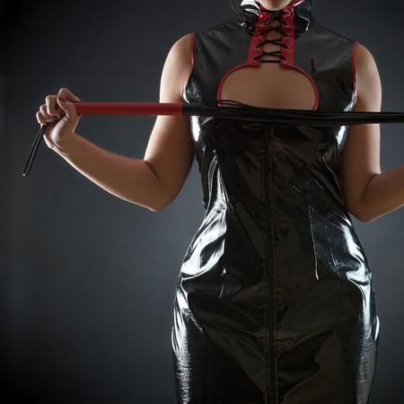 Sexy Frau in rotem Leder Korsett mit Peitsche Standard-Bild