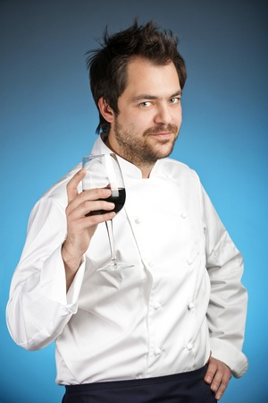Young chef with glass of wine agaist blue background Stock Photo - 12590267