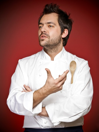 Young chef agaist red  background Stock Photo - 12590269