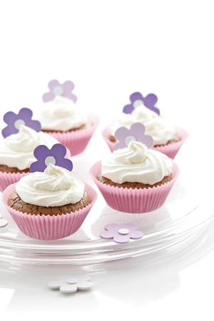Delicious cupcakes with sweet cream and flower decoration photo