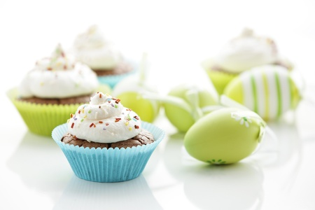 Easter eggs and tasty cupcakes with cream photo