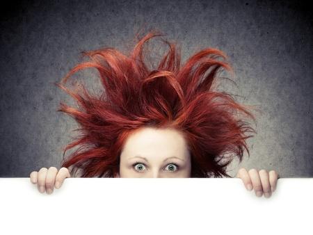 Vöröshajú nő rendetlen haja elleni szürke háttér