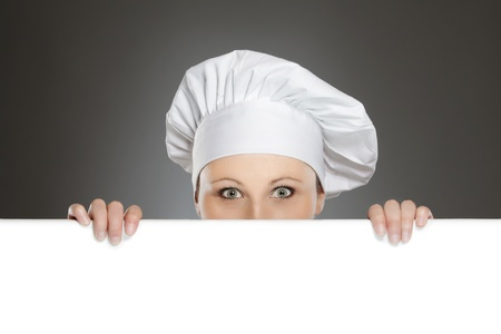 Female chef looking over paper sign billboard photo