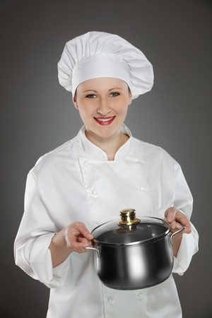 Young female chef holding stainless steel pot Stock Photo - 12883308