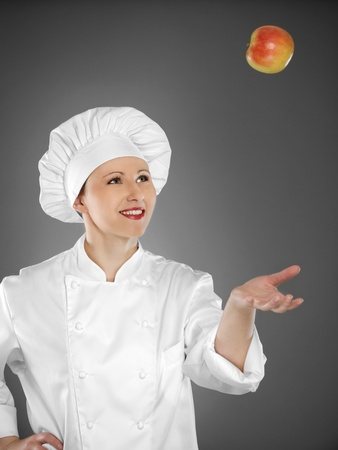 Young female chef playing with apple Stock Photo - 12883311