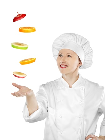 Young female chef catching sliced fruit Stock Photo - 12883304