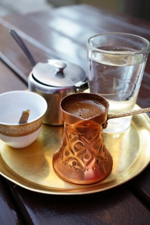 Turkish coffee served in a traditional Turkish metal dish cap  photo