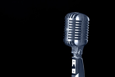 Vintage microphone against black background photo