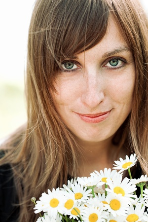 ordinary: Cute young woman with bunch of daisies