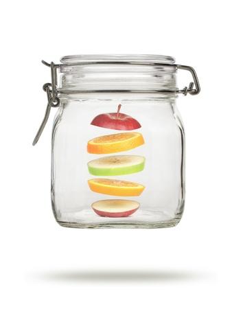 levitating: Levitating fruit in glass jar, isolated on white Stock Photo
