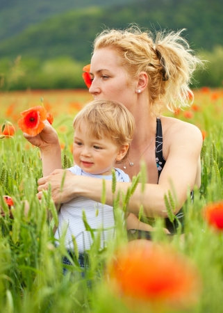 Pretty caucasian woman with her child in poppy field, focus on mother photo