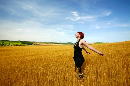Female in wheat field enjoying summer photo