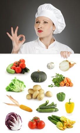 Female chef showing positive gesture over vegetable collection photo
