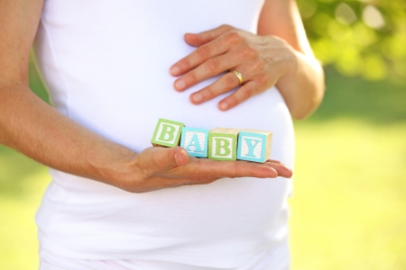 Pregnant woman holding aphabet blocks - word BABY