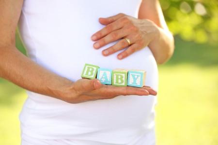 Pregnant woman holding aphabet blocks - word BABY