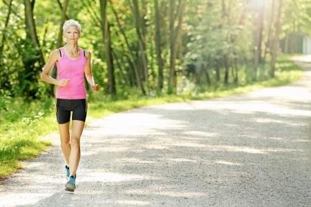jogging track: Fit caucasian woman jogging  in nature