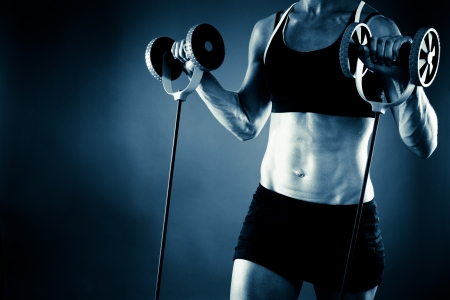 Torso of a young fit woman working out, blue toned image