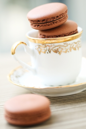 Chocolate macarons in tea cup served on the table photo