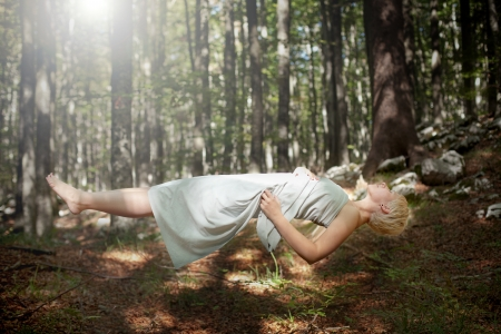 levitating: Levitating woman in the forest Stock Photo