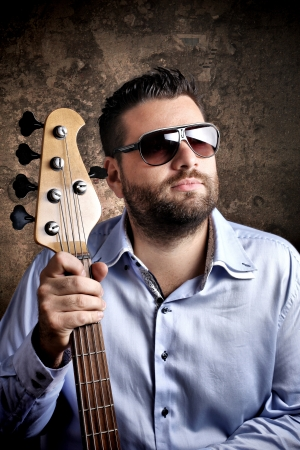 Bass player with glasses posing against grungy background Stock Photo - 15763912