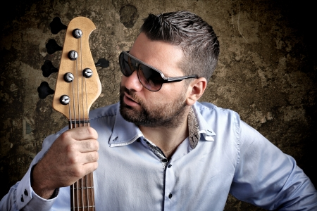 Bass player with glasses against grungy background Stock Photo - 15763913