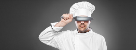 Chef with knife posing against gray background  Stock Photo - 15985405