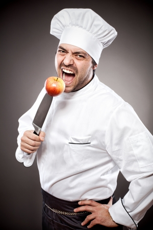 Chef with knife posing against gray background