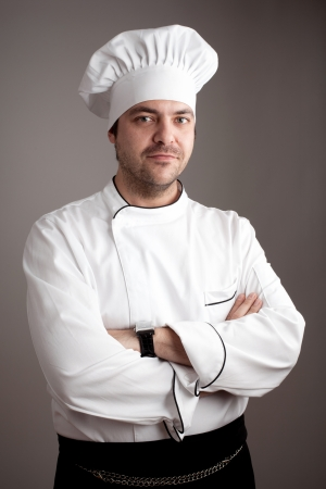 Handsome chef posing against gray background  Stock Photo - 15985413