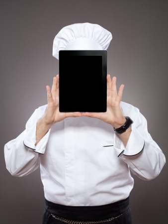 Chef behind the digital tablet against grey background Stock Photo