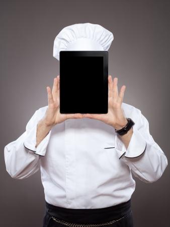 Chef behind the digital tablet against grey background Foto de archivo