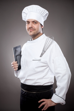 food technology: Chef with digital tablet against grey background