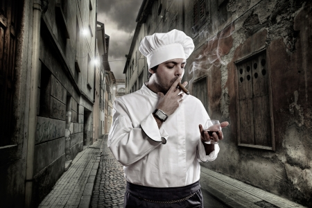 Chef with cognac and cigar smoking in dark street