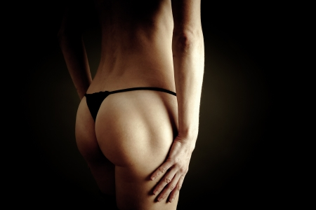 Erotic view of female back on black background Stock Photo - 16239393