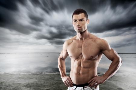 hombre fuerte: Muscular hombre posando contra el fondo oscuro