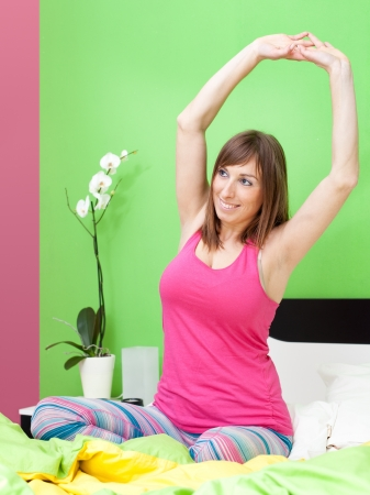 Cute caucasian woman stretching in bed Stock Photo - 17008670