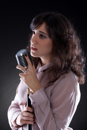 Attractive young brunette woman with a retro microphone Stock Photo - 17055822