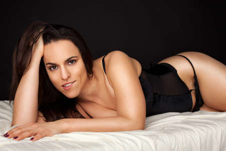 Seductive brunette lying in bed Stock Photo - 17055824