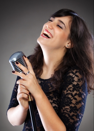 Attractive young brunette woman with a retro microphone Stock Photo - 17369579