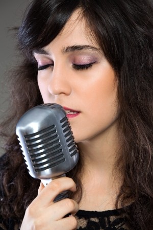 Attractive young brunette woman with a retro microphone Stock Photo - 17369558