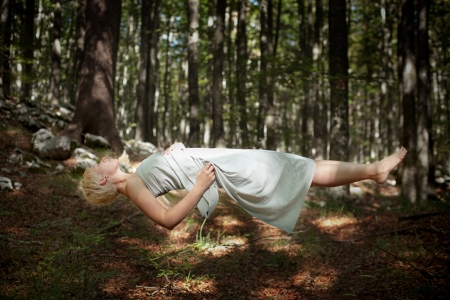 Mujer levitando en el bosque Foto de archivo