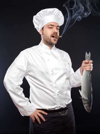 Young handsome chef with sea bass fish smoking cigar Stock Photo - 17647253