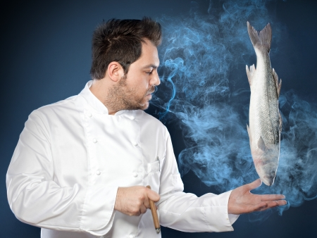 levitation: Young handsome chef with sea bass fish smoking cigar Stock Photo
